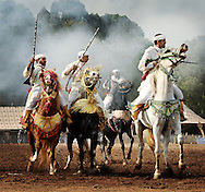 "Riders shoot their guns into the air as a display for Morocco's royalty during the annual Semaine du Cheval, or ""Week of the Horses"" outside of Rabat, Morocco."