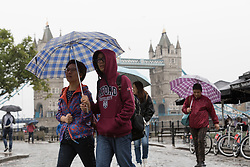 © Licensed to London News Pictures. 30/08/2017. LONDON, UK.  Tourists are caught in heavy rain showers and wet weather near the Tower Bridge at lunchtime. Heavy rain is forecast to fall across areas of the country today.  Photo credit: Vickie Flores/LNP