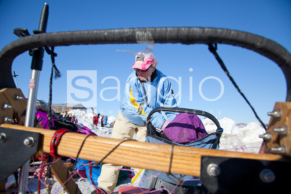DeeDee Jonrowe, bib 2, unpacks her sled during the 2011 Iditarod Trail Sled Dog Race at the check-point in Unalakleet, Alaska.