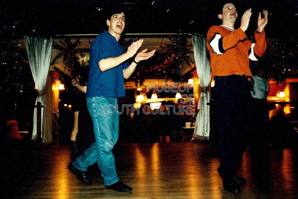 Two young men clapping and standing on dancefloor.