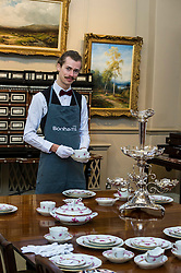 Pictured: Tommy Alexander prepares to serve from a Herend Chinese bouquet pattern dinner service in puce beside a silver epergne by James Deakin and sons, Sheffield 1914.<br /> <br /> Bonhams Scotland's next home and interiors sale is aimed at home makers and interior designers with an emphasis on affordability. Items include a north Italian 17th century later ivory bone inlaid rosewood cabinet on stand valued at GBP5000-6000<br /> <br /> Ger Harley   EEm 31 October 2016