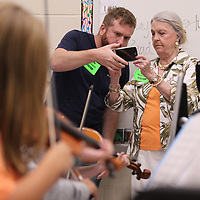 Aaron Phillips, center left, and Margaret Anne Murphey shoot photos of the string class being taught at Tupelo Middle School as part of her video segment on the Tupelo Symphony for the Mississippi Bicentennial video being produced around the state.