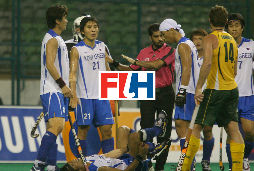 Kuala Lumpur:   Umpire Satinder Kumar cooling the tempers of the Korean players when Chul Kim got injured in the match against Australia in the Samsung Hockey Men Champions Trophy on Nov 30th, 2007.  Photo:GNN/Vino John