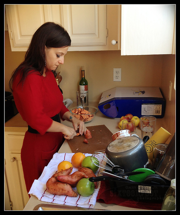 Gary Cosby Jr.  iPhone photographs  A young woman prepares a holiday meal in her kitchen.