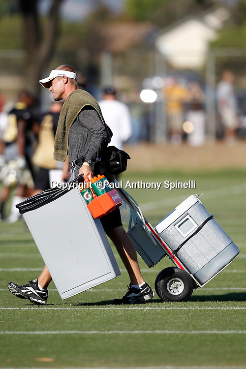 A trainer hauls water containers on the field at the New Orleans Saints west coast NFL training camp on Wednesday, August 24, 2011 in Oxnard, California. (©Paul Anthony Spinelli)