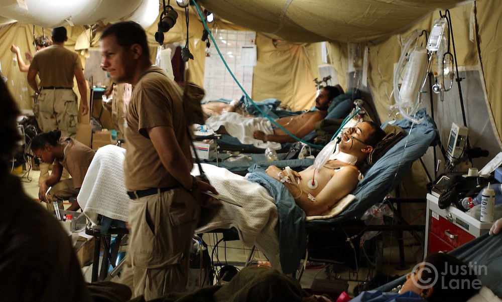 08/20/03--Att: FORIEGN--28th COMBAT SUPPORT HOSPITAL, IRAQ--23-year-old Suta Hida, an Iraqi man who works for the United Nations, at center, lies in a bed at the 28th Combat Support Hospital, which lies SW of Baghdad, recovering from facial lacerations, and other injuries, he suffered when the UN compund in Baghdad was bombed yesterday.