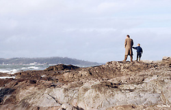 Father and son walking on cliff top,
