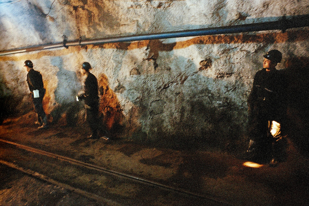 350 metres under the surface, miners wait for a train that will take them to an express lift that will take them back up to the surface again. Shanxi, China. 2006.