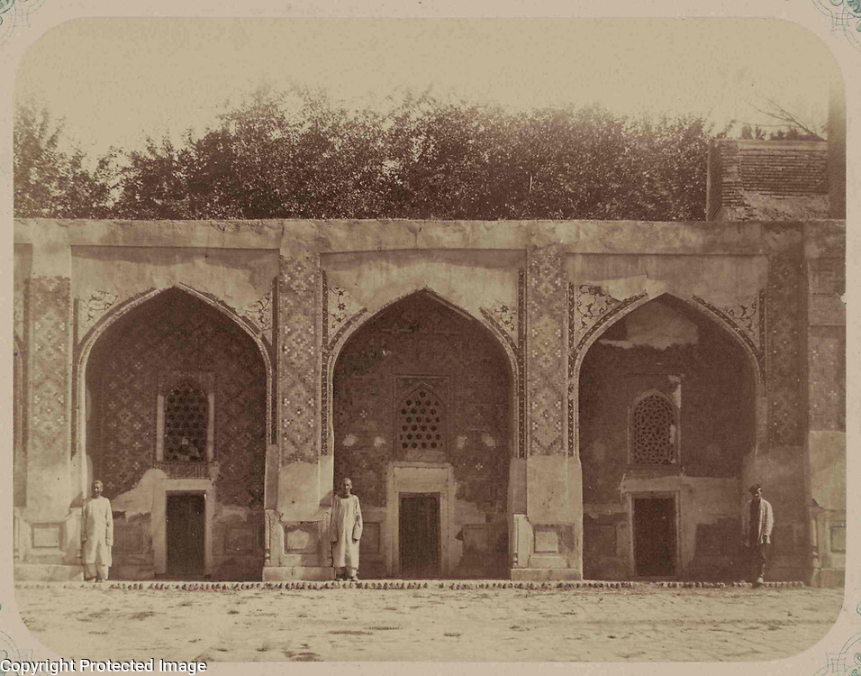 1868<br /> This photograph of the Nadir Divan-Begi Madrasah in Samarkand (Uzbekistan) is from the archeological part of Turkestan Album. The six-volume photographic survey was produced in 1871-72 under the patronage of General Konstantin P. von Kaufman, the first governor-general (1867-82) of Turkestan, as the Russian Empire&rsquo;s Central Asian territories were called. The album devotes special attention to Samarkand&rsquo;s Islamic architectural heritage. Located next to the Khodzha Akhrar shrine, this madrasah (religious school) was completed in 1631 by Nadir Divan-Begi, vizier to the Bukharan ruler Imam-Quli Khan. The madrasah was planned as a rectangular courtyard enclosed by a one-story arcaded cloister for scholars and a mosque at one end. This view shows three cells (khujras) on the left side of the south cloister. Each arched cell has a lattice window above the low door. The standing figures give an idea of the scale. Although the facade shows major losses of ceramic ornamentation, it is clear that the arch niches, as well as the outer facade, were covered in a rich array of polychrome tiles with floral and geometric designs. The lower part of the wall was originally surfaced in stone. A brick passageway elevates the arcade from the cobbled courtyard. On the far right is the edge of the iwan arch at the center of the south cloister.