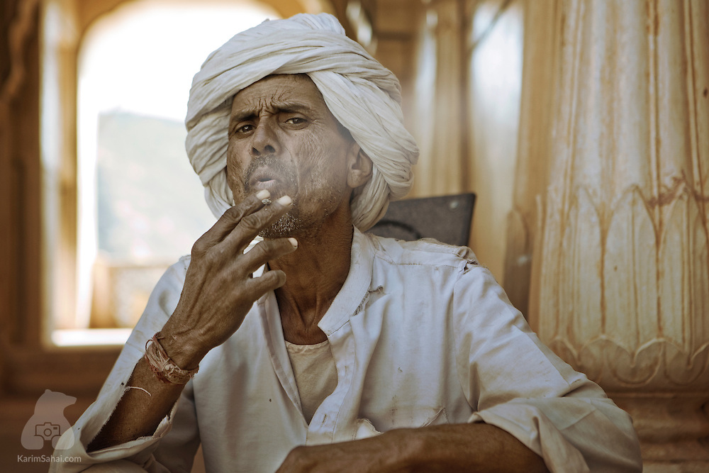 A man with a turban smokes a 'bidi' at the Amer Fort in Jaipur, Rajasthan, India.