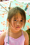 Quiet young Hmong child age 2 under sun umbrella. Hmong Sports Festival McMurray Field St Paul Minnesota USA