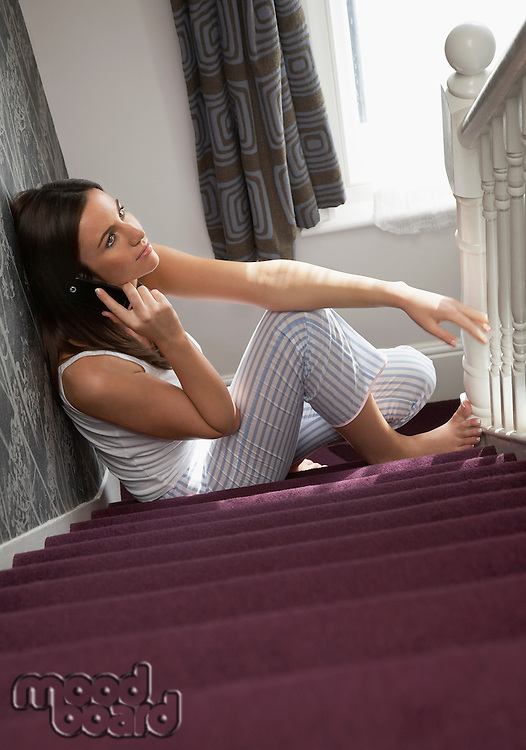 Young woman using telephone sitting on stairs in home
