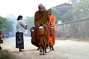 Buddhist monks receive rice from a woman alongside the main dirt street in Champasak, Laos. Champasak is home to Wat Phou, one of the most important Buddhist temples in Asia, and a UNESCO World Heritage site.