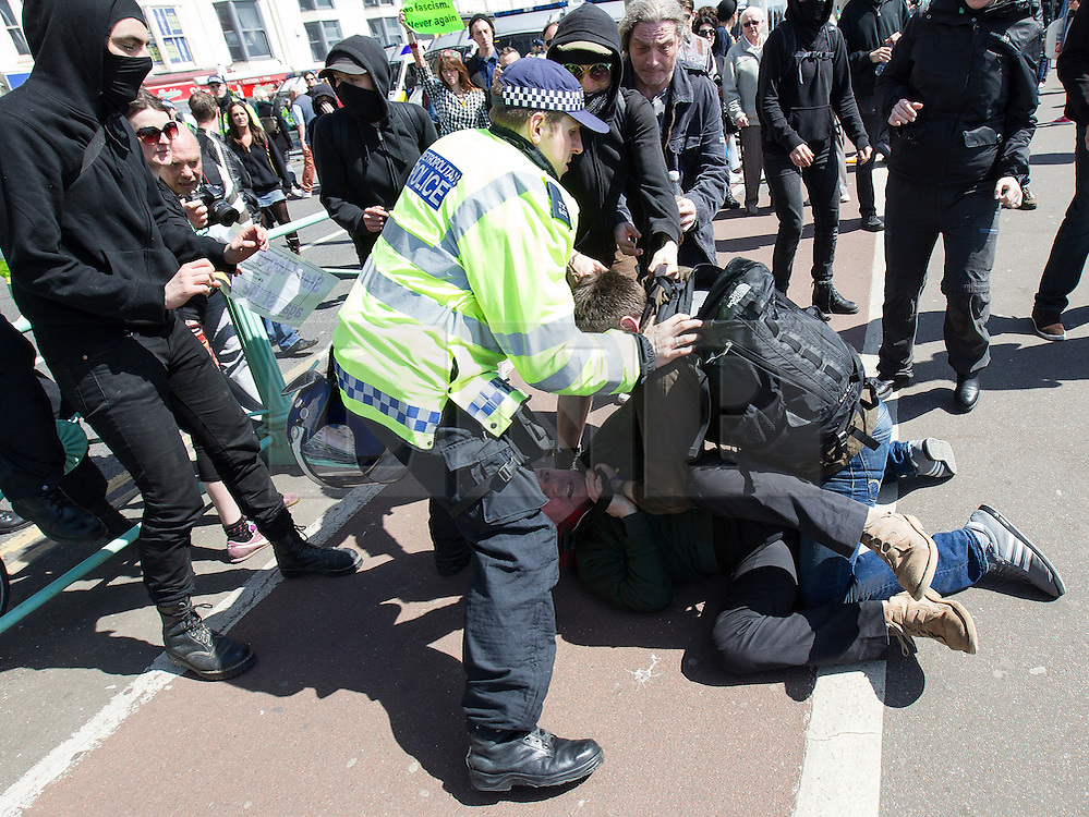 © Licensed to London News Pictures . 21/04/2013 . Brighton , UK . A policeman intervenes as those for and against the march have a fist fight in the road on the seafront . Nationalist group March for England hold a march along Brighton seafront today (Sunday 21st April) . The group was supported by supporters of the English Defence League and opposed by anti fascist and left wing groups . The annual march takes place close to St George's Day and frequently results in scuffles and violence between opposing groups and police . Photo credit : Joel Goodman/LNP