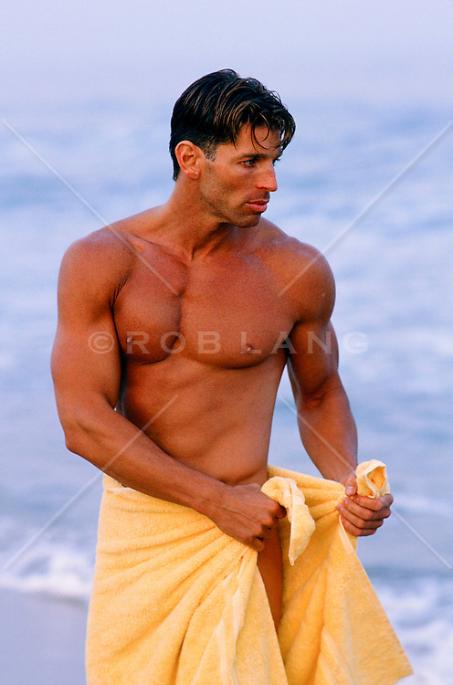 good looking man wrapping a towel around his waist on the beach