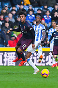 Terence Kongolo of Huddersfield Town (5) fouls Alex Iwobi of Arsenal (17) during the Premier League match between Huddersfield Town and Arsenal at the John Smiths Stadium, Huddersfield, England on 9 February 2019.