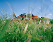 BAE Systems Hawk of the Red Arrows, Britain's RAF aerobatic team, seemingly hidden in long airfield grass.