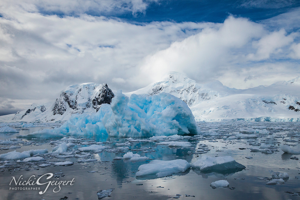 Iceberg with reflection on glassy ocean with mountains and glaciers in background, Antarctica. Seascapes and Icescapes wall art. Fine art photography prints, stock images