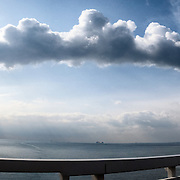 Photo taken from the Isewangan Expressway in Mie Prefecture, Japan. Billowing cloud formation resulting from condensation of water vapor upon emissions from a coal-fired electricity generating plant visible in the distance.