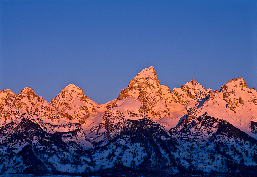 The Teton Mountain Range just outside Jackson Hole Wyoming is also close to Yellowstone National Park with the tallest peak the Grand Teton at 13,770 ft (4,197 m) seen on cold winter sunrise morning