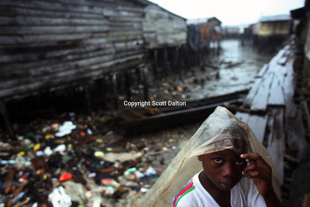 A young boy covers himself from the rain in Lleras, a poor barrio in Buenaventura, on the Pacific Coast of Colombia, on Tuesday, May 15, 2007. Buenaventura is in the midst of a spree of violence over control of drug shipments from the poor barrios in the city. Many of the neighborhoods have a strong presence of FARC militias that control most of the drug trade in the city. (Photo/Scott Dalton)