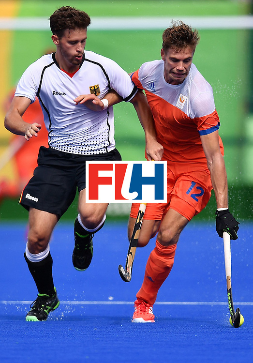 Germany's Timm Herzbruch and Netherlands' Sander De Wijn (R) vie during the mens's field hockey Germany vs Netherlands match of the Rio 2016 Olympics Games at the Olympic Hockey Centre in Rio de Janeiro on August, 12 2016. / AFP / MANAN VATSYAYANA        (Photo credit should read MANAN VATSYAYANA/AFP/Getty Images)