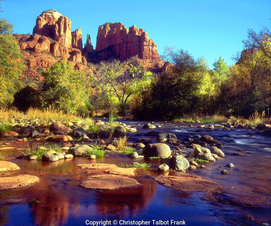 I hiked up the stream to take this photo of the Sedona Landscape showing Cathedral Rock reflecting in Oak Creek.  The beautiful Arizona landscape shows classic sandstone formations with a lush river flowing through it.