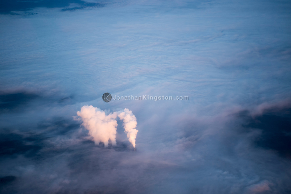 Aerial of pink sunrise light illuminating smoke rising from smokestacks over a background of ground fog at a major coal and natural gas fired power plant near Centralia, Washington.