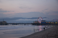 Dusk at the Santa Monica Pier.  Photo taken from the beach looking out to the ferris wheel with the cloud covered Santa Monica Mountains behind. Santa Monica, CA 1.9.15