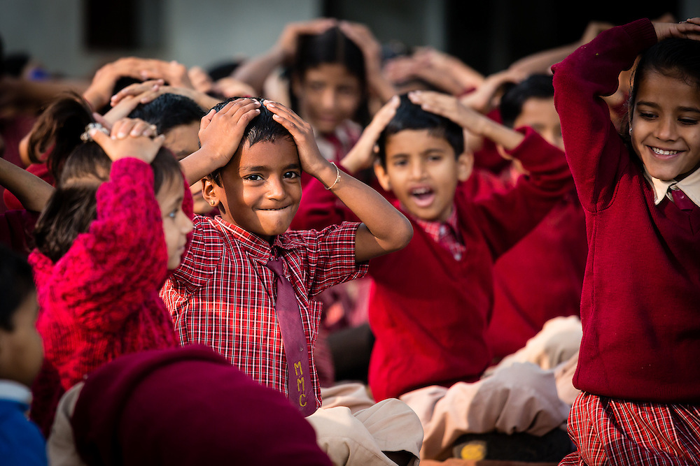 In the morning, near a hindu temple, school children pratice some gymnastics, following the exercises of two older students.