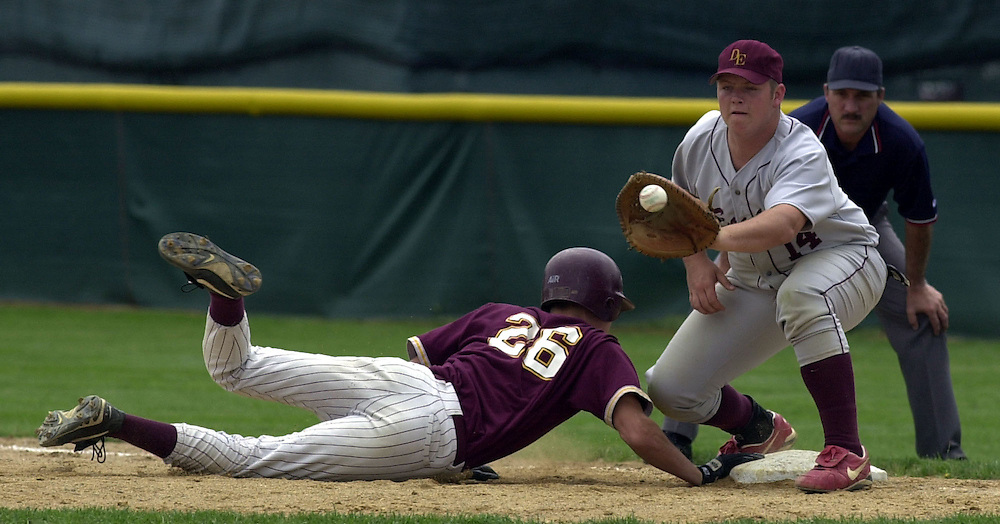 Lester Prairie's David Paulson gets his hand on the base before the ball in an attempt by the pitcher to throw him out while Dover-Eyota's Dallas Waldemar and an umpire wait for the ball at the semi-final game of the Class A Minnesota State High School League Tournament in Chaska, Minn., on Friday, June 16, 2000.  Lester Prairie defeated Dover-Eyota 2-0 to advance to the finals.(AP Photo/Adam M. Bettcher)
