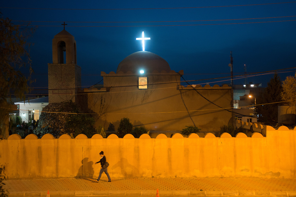 A woman walks past the 1300 year old Saint George Chaldean church in Ainkawa, a largely Christian town on the outskirts of Erbil, the capital of Iraqi Kurdistan. Iraq's Christian community is made up of numerous different churches, including the Assyrian Church of the East, the Syrian Orthodox Church, the Syrian Catholic Church, the Armenian Apostolic Church, however the majority of Iraq's Christians belong to the Chaldean Catholic church. Iraq's Christian community is considered one of the longest continues Christian communities in the world. In 2003 there were an estimated 1.5 million Christians in Iraq. Today, Iraqi Christians are thought to number approximately 400,000. Violence, persecution and sectarian strife have forced more than two thirds of the Christian population to flee the country.  Ainkawa, Iraq. 17/04/2014.