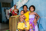 """Caridad Miranda, 53, photographed in her home with some of her family members and the laundry from her youngest grandchildren, lives with her husband, eightchildren and eight grandchildren. She studied theater at the prestigious""""Instituto Superior de Arte"""" and has been a singer and actor, even performing in several Cuban movies. """"The hardest thing in my life right now is our housing situation because there are just too many people living here and not enough food. We gets food rations but it's not enough for all of us."""" Of Cuban women, she says """"being a Cuban woman means being everything for one's family."""""""
