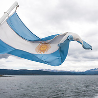 An Argentine flag waves from the back of a sightseeing boat on the Beagle Channel in Parque Nacional Tierra del Fuego, near Ushuaia, Argentina.