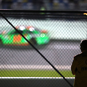 A crew member watches Danica Patrick race down the front stretch during the NASCAR Sprint Unlimited Race at Daytona International Speedway on Saturday, February 15,  2014 in Daytona Beach, Florida.  (AP Photo/Alex Menendez)