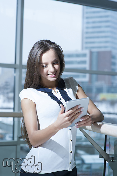 Businesswoman smiling and reading from tablet