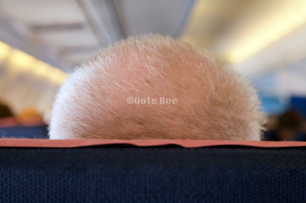 elderly persons head seen from behind sitting in an airplane