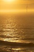 Wind Turbine in the ocean on a misty morning.