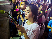 29 MAY 2018 - BANGKOK, THAILAND: People hold lotus blossoms while they pray during Vesak observances at Wat Hua Lamphong in Bangkok. Vesak is the Buddha's birthday, and one of the most important holy days in the Theravada Buddhist religion. Many Thais visit their local temples for Vesak and rededicate themselves to the Dharma, listen to talks about Buddhism and make merit by bringing flowers to the temple.       PHOTO BY JACK KURTZ