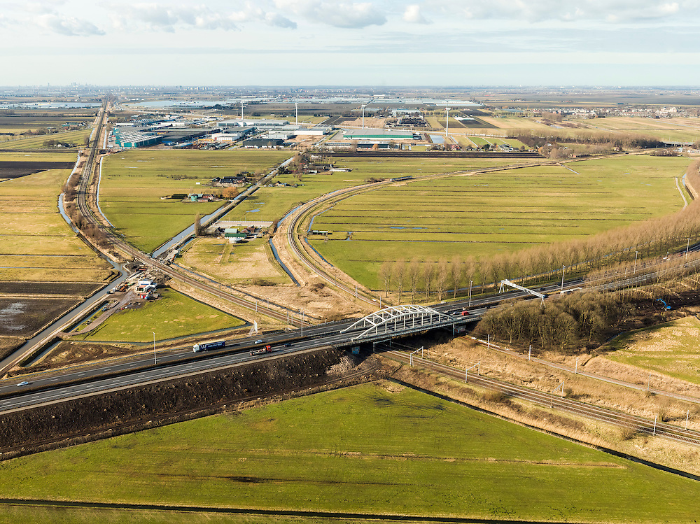 Nederland, Zuid-Holland, Gouda, 20-02-2012; Zuidplaspolder, Gouweknoop. .Rijksweg A20, met boogbrug over de intercity spoorlijn naar Zoetermeer en Den Haag (aan de horizon). Naar rechts de enkelsporige spoorlijn Gouda - Alphen aan den Rijn.Roadway A20 in the polder, crossing the railway. Business park at the horizon..luchtfoto (toeslag), aerial photo (additional fee required) .copyright foto/photo Siebe Swart