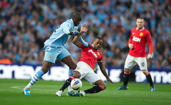 MANCHESTER, ENGLAND - Monday, April 30, 2012: Manchester City's Yaya Toure in action against Manchester United's Patrice Evra during the Premiership match at the City of Manchester Stadium. (Pic by Chris Brunskill/Propaganda)