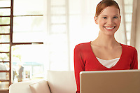 Young woman using laptop at home portrait