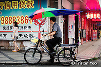 A typical chinese rider looking out to find his next customer to ferry. I love the improvished long umbrella. Maybe I should have one of them for my shoot.