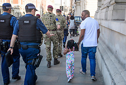 © Licensed to London News Pictures. 25/05/2017. London, UK. Armed soldiers and police walk past a young girl in Westminster, London following a terrorist attack in Manchester, northern England, earlier this week. 23 people were killed an dozens more injured when Salman Abedi set off a suicide bomb at an Ariana Grande concert.  Photo credit: Ben Cawthra/LNP