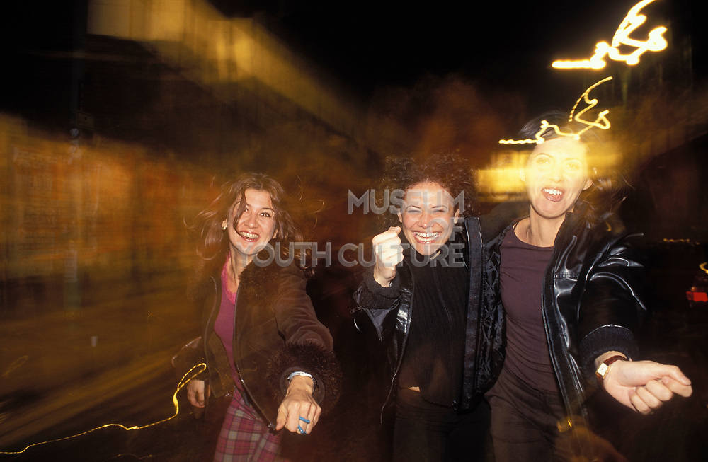 Three girls, smiling and laughing, out on the town, UK 2004