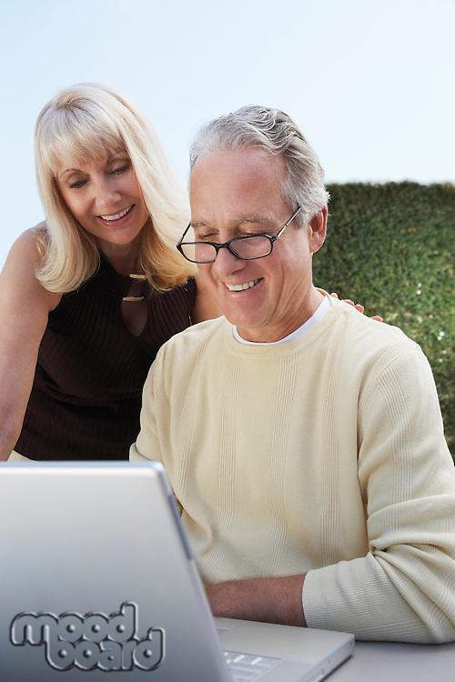 Couple Using Laptop in Garden
