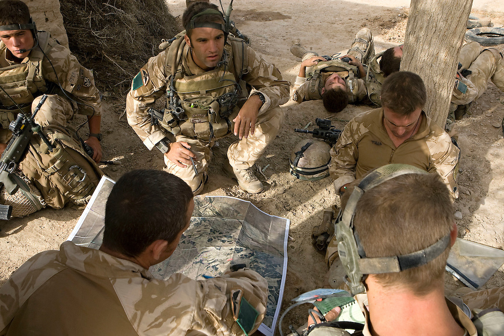 British soldiers of 3rd Battalion The Parachute Regiment plan their next move whilst searching for insurgents after a dawn assault on a compound as part of Operation 'Southern Beast'. Kandahar Province, Afghanistan on the 6th of August 2008.