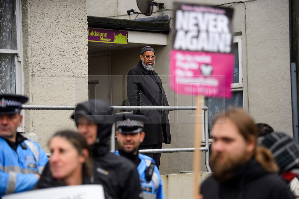 **NOTE TO EDITORS: An young girl is pictured in the image** © Licensed to London News Pictures. 07/01/2017. London, UK. A male member of the mosque looks out as members of Kent Anti-Racism Network demonstrate at Mote Road Islamic centre mosque in Maidstone, Kent as far-right group The South East Alliance protest against expansion of the mosque. Plans to redevelop Maidstone Mosque into a purpose-built centre with three shops have been approved by  Maidstone Borough Council. A counter demonstration is Organised by The Kent Anti-Racism Network. . Photo credit: Ben Cawthra/LNP