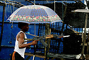A Liberian government gunman holding an umbrella, a rifle and a crutch for the bullet wound in his leg fires over the 'Old Bridge' in  torrential rains, Monrovia 28 July 2003. LURD(Liberians United for Reconciliation and Democracy) rebels drove government forces back over the bridge last night leaving the government forces on the Monrovia side of the bridge defending the city.This the Tenth day of continued fighting for the capital despite the call for ceasefire and heavy rainfall.<br /> EPA PHOTO/NIC BOTHMA