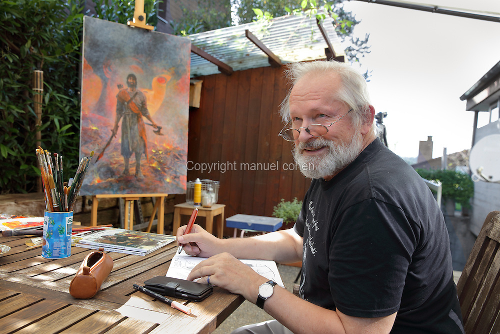 Portrait of Grzegorz Rosinski, Polish comic book artist, born 1941 in Stalowa Wola, Poland, signing a picture next to a painting from the Thorgal series in his outdoor studio area on a verandah in his garden at his home in Mollens, Sierre, Switzerland, 9th September 2016. Rosinski is the author and designer of many Polish comic book series, and created Thorgal with Belgian writer Jean Van Hamme in 1977. The stories cover Norse mythology, Atlantean fantasy, science fiction, horror and adventure genres. Picture by Manuel Cohen